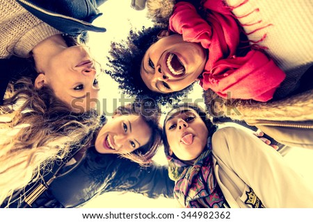 Group of attractive young women of different ethnics hugging in a circle - Four students smiling at camera - Best friends spending time together - stock photo