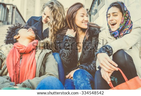 Group of attractive young women of different ethnics laughing and having party - Four students sitting outside university - Best friends spending time together - stock photo