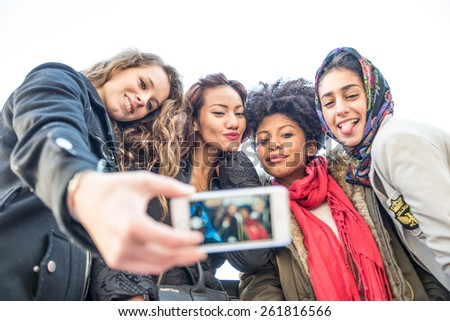 Group of attractive young women of different ethnics taking a selfie - Students having fun - Best friends spending time together - Tourists photographing on a city tour - stock photo