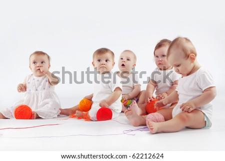 Group of babies sitting on white studio background - stock photo