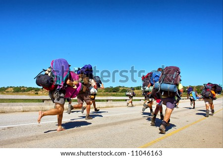 Group of backpackers runs across the bridge. Shot in the Langeberge highlands near Gouritsrivier river, Garden Route, Western Cape, South Africa. - stock photo