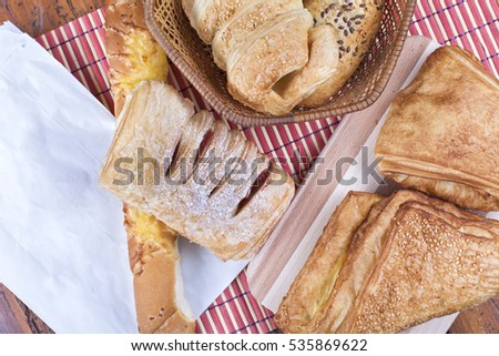 Group of bakery products on a wooden table with paper bag