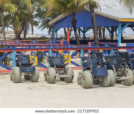 Group of beach wheelchairs on sand with palm trees on background - stock photo