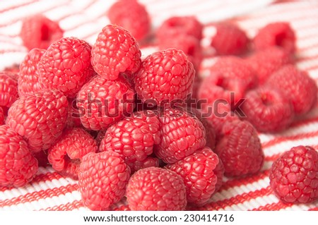 group of beautiful raspberries on a striped light background diagonal with a focus on the first layer of berries