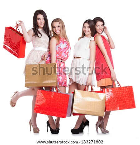 Group of beautiful shopping women with bags on white background - stock photo