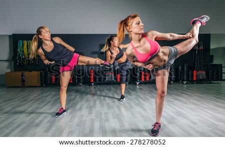 Group of beautiful women in a hard boxing class on gym training high kick - stock photo