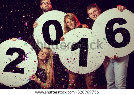 Group of beautiful young people celebrating New Year's Eve, holding four cardboard circles with numbers 2016 written on them - stock photo