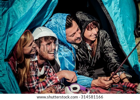 Group of best friends taking a selfie in camping while it is raining - Concept of carefree youth and freedom outdoors in the nature - Young people during vacations - stock photo