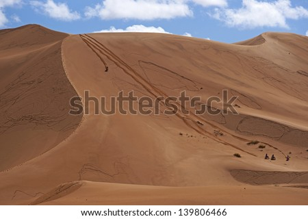 Group of bikers descend a steep sand dune in the Sahara Desert of Morocco in North Africa