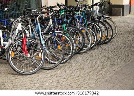 Group Of Bikes Parked In A Row In A Parking Lot - stock photo