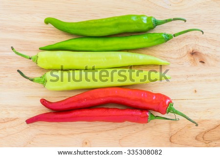 Group of both red and green freshly picked ripe chili peppers on wooden background. Red chilies contain large amounts of vitamin C and small amounts of carotene (provitamin A). - stock photo