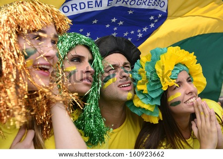 Group of Brazilian soccer fans concerned with the national team performance with the flag of Brazil swinging in the air. - stock photo