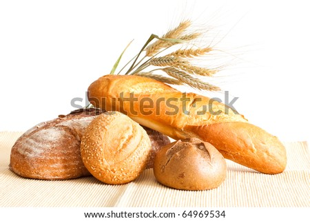 Group of bread and wheat spikes on a white background. - stock photo
