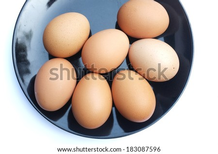 Group of brown eggs in the plate isolated on white - stock photo