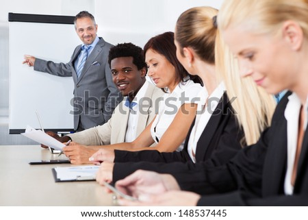 Group of business executives taking notes during a meeting at office
