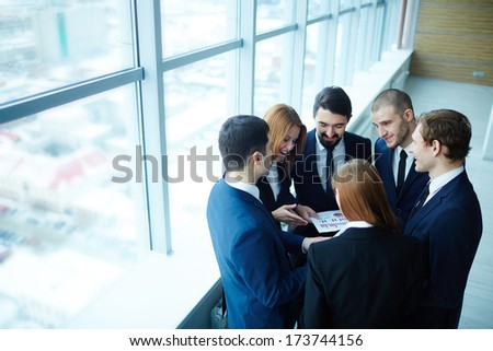 Group of business partners discussing paper at meeting in office - stock photo