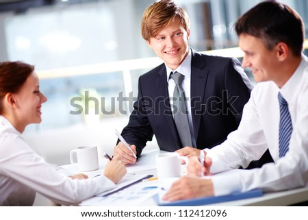 Group of business partners interacting at meeting with focus on young man - stock photo