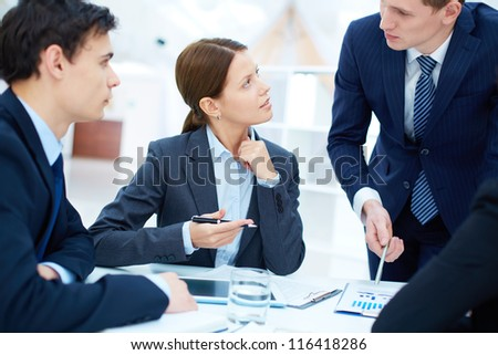 Group of business partners listening to young manager at meeting