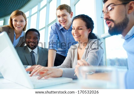 Group of business partners looking astonishingly at laptop display at meeting - stock photo
