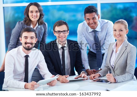 Group of business partners looking at camera with smiles while working in office