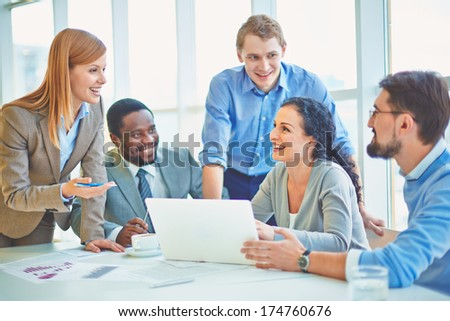 Group of business partners looking at smiling female explaining her ideas at meeting - stock photo