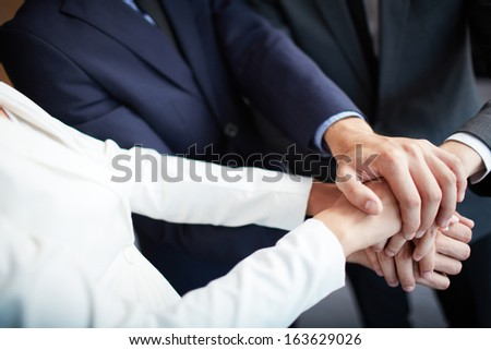Group of business partners making pile of hands - stock photo