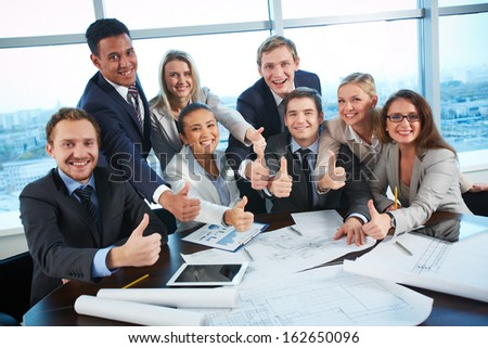 Group of business partners showing thumbs up while sitting at workplace in office - stock photo
