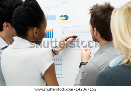 Group Of Business People Analyzing Graph and Annual Report - stock photo