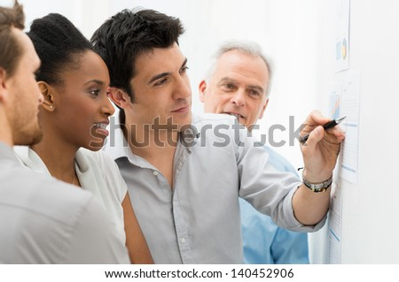 Group Of Business People Analyzing Graphs and Charts in Office - stock photo