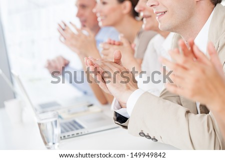 Group of business people applauding in a meeting. - stock photo
