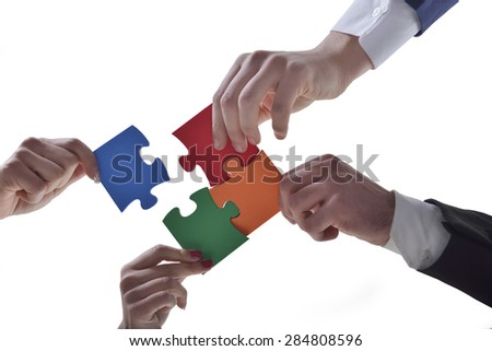 Group of business people assembled jigsaw puzzle and represent interpersonal cooperation and success