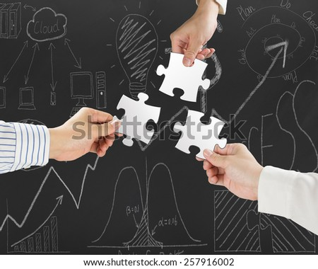 Group of business people assembling blank white jigsaw puzzles on business concept doodles background - stock photo