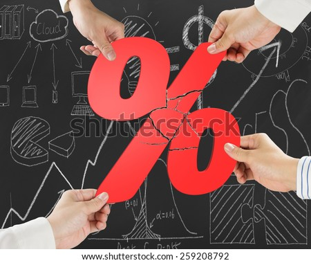 Group of business people assembling broken red percentage sign with doodles background - stock photo