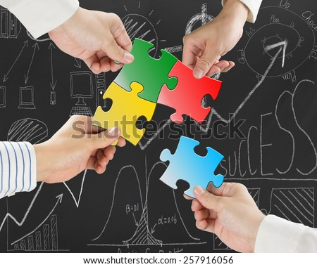 Group of business people assembling colorful jigsaw puzzles on business concept doodles background - stock photo