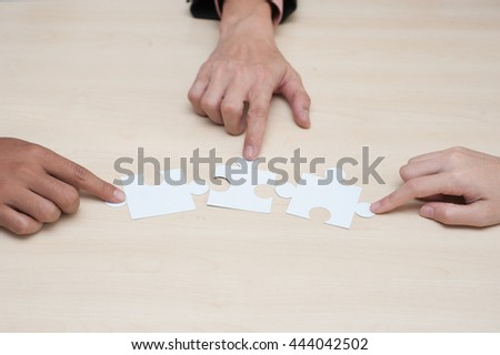Group of business people assembling jigsaw puzzle and represent team support and help concept in office. - stock photo