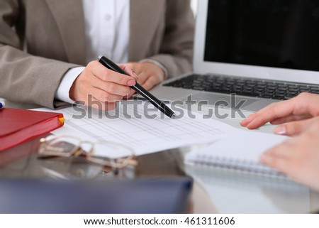 Group of business people at meeting  discussing financial results. Women pointing into laptop computer monitor