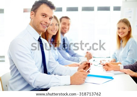 Group of business people at meeting looking at camera - stock photo