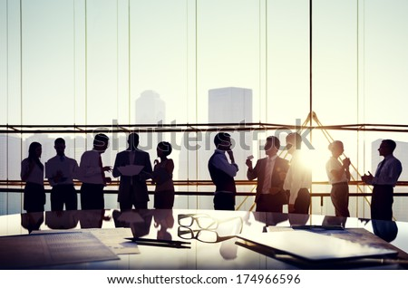 Group of Business People Discussing at Sunset Reflected Onto Table with Documents. - stock photo