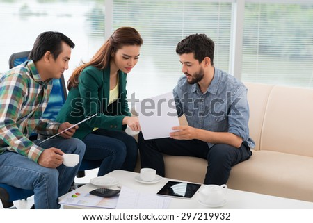 Group of business people discussing financial documents in the office - stock photo