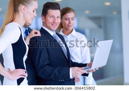 Group of  business people doing presentation with laptop during meeting .