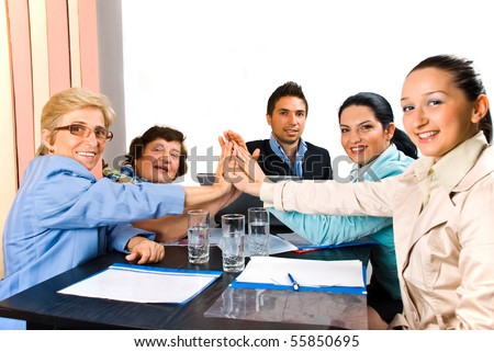 Group of business people giving high five and smiling  at  meeting or team spirit - stock photo