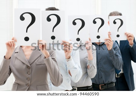 Group of business people hiding their faces behind a question mark sign at office - stock photo