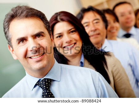 Group of business people lead by a man at the office - stock photo