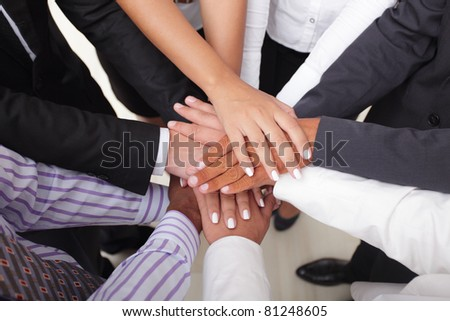 Group of business people making a pile of hands - stock photo