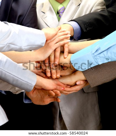 group of business people making a pile of hands in a light and modern office environment - stock photo