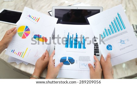 Group of business people pointing at business document during meeting - stock photo