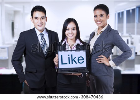 Group of business people showing like on laptop at office - stock photo