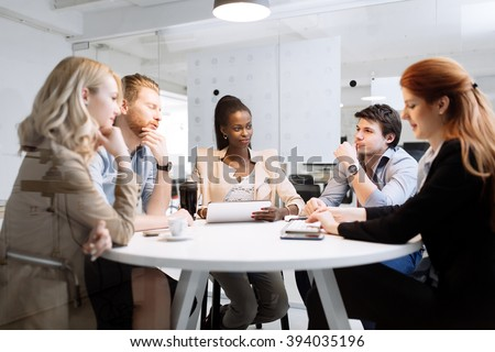 Group of business people sitting at desk and discussing new ideas - stock photo