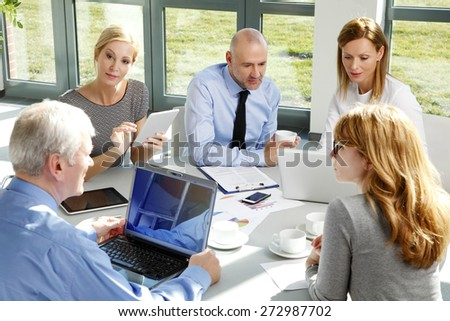 Group of business people sitting at office.  Businesswomen and businessman consulting with each other and working on new plan while sitting around the conference table and using laptop and tablet.  - stock photo