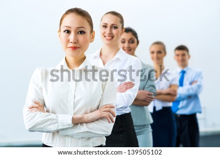 group of business people standing in a row, smiling and crossing his arms